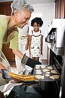 Grandmother baking cookies for grandchildren