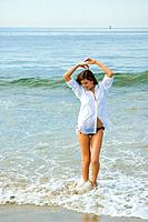 Young woman wading on beach