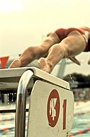 Male swimmer jumping from starting block