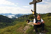 Wanderer at summit cross of mountain Burgspitz, 1429 m, national park Limestone Alps, Upper Austria, Austria