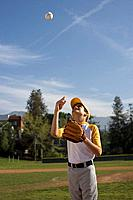 Portrait of boy with baseball mitt throwing ball