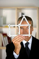 Senior businessman holding a model of a house
