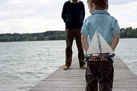 Little boy is standing in front of a man with a miniature sailing boat behind his back, both on a footbridge, selective focus