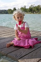 Little blond girl eating an ice lolly on a wooden footbridge