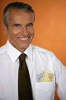 Smiling senior businessman with banknotes in his front pocket