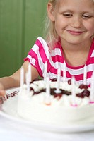 Little blond girl in front of a birthday cake, close_up