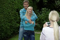 Blond girl taking a picture of her parents in a park, selective focus