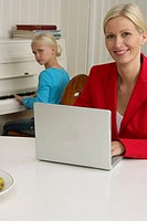 Blond girl is playing piano behind her mother who is working with a laptop, selective focus