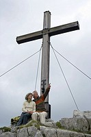 Senior adult couple sitting under a huge wooden cross in the mountains, low angle view