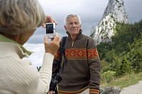 Senior adult woman taking a picture of her husband in the mountains, selective focus