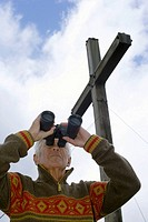 Senior adult man standing under a wooden cross and is looking through binoculars, low angle view