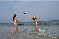 Two young women playing volleyball at the beach (thumbnail)
