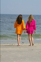 Two young women promenading at the beach in bathrobes