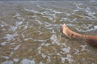 Naked leg of a young woman in the shallow water of the sea, high angle view