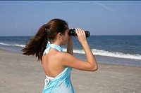 Young brunette woman looking through binoculars, selective focus