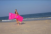 Young woman carrying an airbed at the beach
