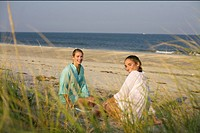 Two young women sitting behind a dune at the beach