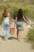Two young women walking over dunes while carrying a basket