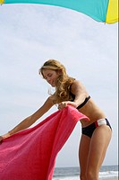 Young blond woman unfurling her towel at the beach, low angle view