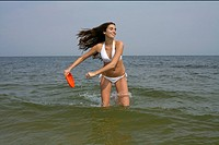 Young brunette woman in the sea holding a Frisbee, selective focus