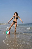 Young woman kicking a volleyball with her foot