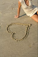 Woman sitting next to a heart drawn into the sand , high angle view