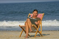Woman sitting on a beach chair while reading