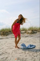 Young blond woman is changing clothes at the beach