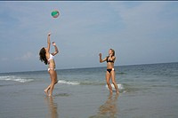 Two young women playing volleyball at the beach