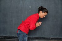 Asian woman bowing in front of a blackboard