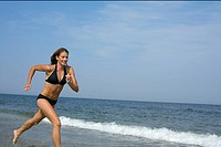 Young woman jogging at the beach