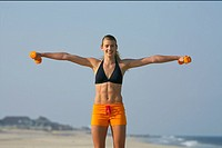 Young blond woman training with tiny barbells at the beach
