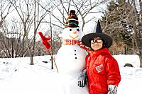 A child standing by a snowman