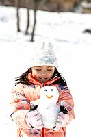 A girl holding a small snowman