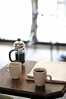 cafe table with coffee mugs and newspaper.