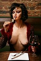 Young topless woman smoking and drinking at burlesque bar