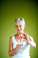 Mature woman holding large pill and glass of water
