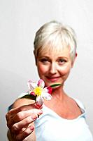 Mature woman holding flower.