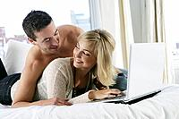 Young happy couple using laptop in bed.