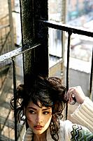 Young stylish woman sitting on fire escape