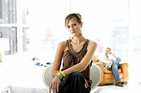 Young stylish woman sitting in chair with man behind (thumbnail)