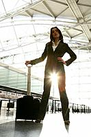 Young businesswoman standing in sunlit airport.