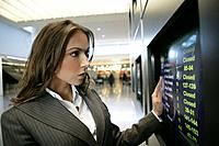 Young businesswoman looking at departures screen at airport