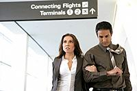 Young business couple walking in airport (thumbnail)