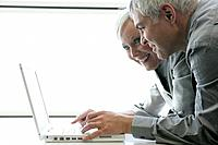 Happy mature couple looking at laptop