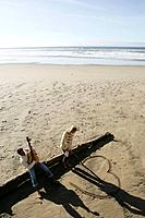 Young couple relaxing on beach in winter (thumbnail)