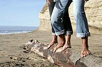 Cropped view of couple balancing on log at beach