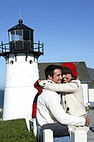 Young couple hugging at lighthouse.