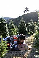 Young couple about to kiss in Christmas tree lot.