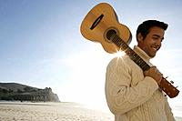 Young man with guitar at beach.